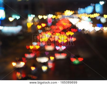 Abstract blurred background with heart bokeh shape of car and traffic lights