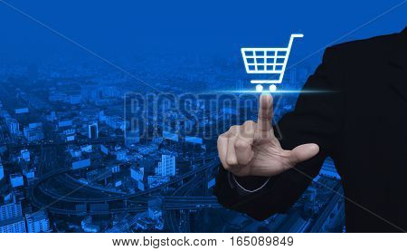 Businessman pressing shopping cart icon over city tower and street blue tone background Shop online concept