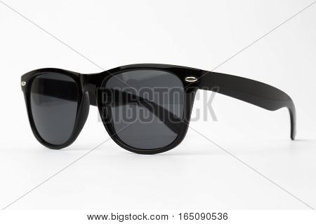 Cool sunglasses with black plastic frame isolated on white background, top view