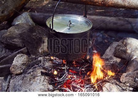 Cauldron boils on the fire in the forest. In marching a saucepan preparing food. Adventure tourism, camping, cooking on a fire. Survival in the forest. Stalker