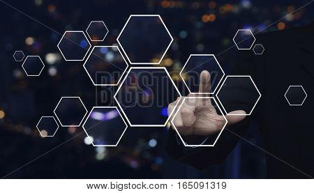 Businessman hand pushing blank hexagon shape virtual technology screen over blur light city tower background