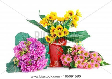 Yellow fabric flowers in vase and pink flowers isolated on white background.