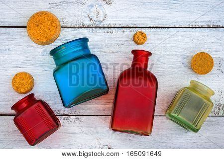 Colored glass bottles with stoppers are open on the painted table