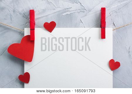 Valentine love background with white sheet of paper and red paper hearts hanging onto clothespins on a rope. Horizontal orientation gray concrete background place for text.