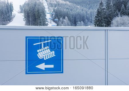 Blue signboard to the chair lift in the mountains