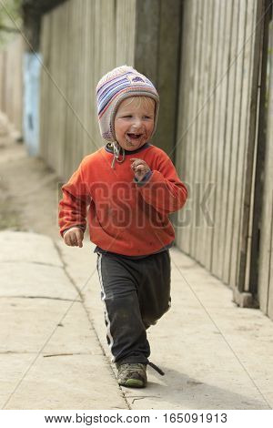 STINKA UKRAINE - APRIL 14 2016 - funny little dirty boy walks dancing along the street on April 14 2016 in Stinka village