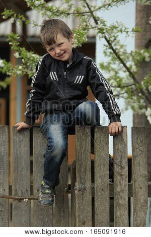 STINKA UKRAINE - APRIL 14 2016 - little country kid sits on a fence at the yard on April 14 2016 in Stinka village