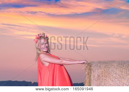 Sexy woman on hay stack on sunset. Beauty romantic girl outdoors against hay stack. Photo of sexy blond in a field with haystacks