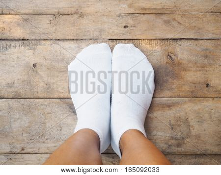 Selfie feet wearing white socks on wooden floor background