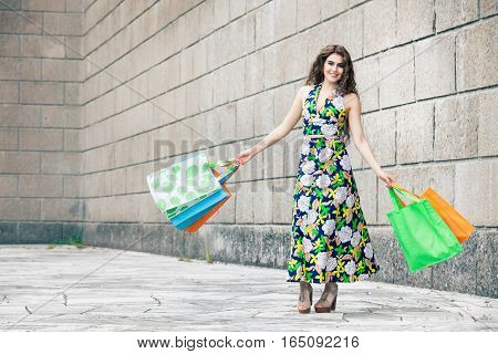 Shopaholic. Shopping love. Beautiful happy woman with bags. A happy and smiling woman just went shopping. Beautiful smile. Colored bags in hand. Long curly hair and stylish clothes flowered dress. Outdoors in the city in front of a large brick wall.