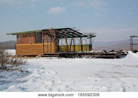 Semi destroyed wooden gazebo. Summer pavilion in winter day.