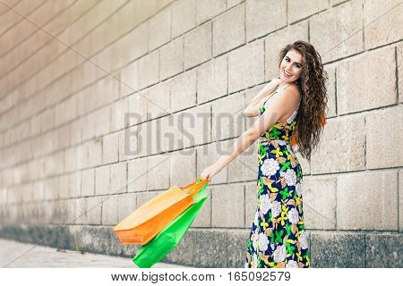 Happy and smiling woman just went shopping. Beautiful smile. Colored bags in hand. Long curly hair and stylish clothes flowered dress.. Outdoors in the city in front of a large brick wall. Shopaholic. Shopping love.