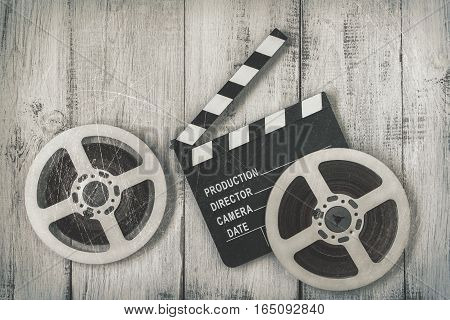 Clapperboards and two reels of film.Black and white stylized photo