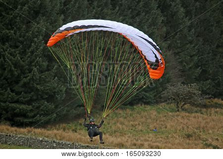 Paraglider on descent approaching his landing field
