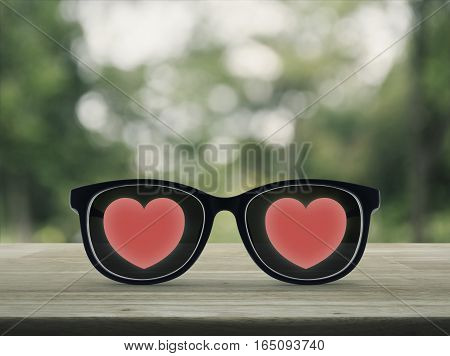 Love heart with eye glasses on wooden table over blur green tree background soft tone Valentines day concept