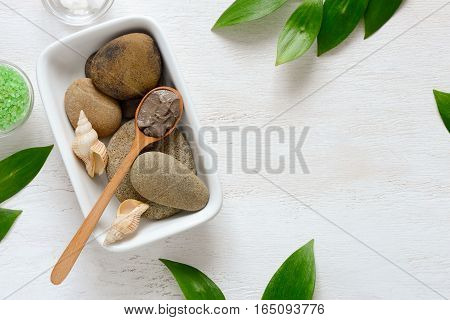 Spa composition with Dead sea mud or cosmetic clay in a spoon view from above space for a text