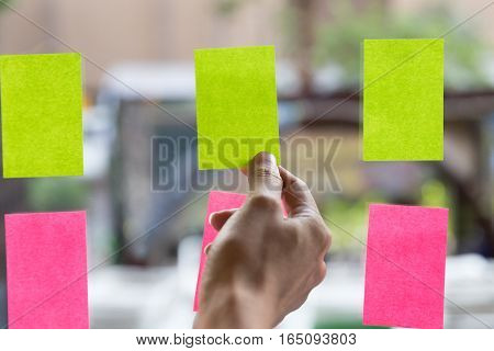 young businesswoman with colleague sticking adhesive notes on window in office