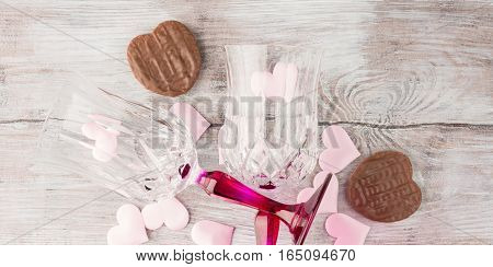 Two stemmed champagne glasses with pink hearts and chocolate cookies on wooden textured background. Valentine's day wedding romantic date invitation. Top view banner