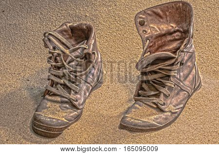 soldier hat  boots and sand glass in the desert Wreck bulletproof helmet Military boots and goggles sand in the desert It sank in the sand