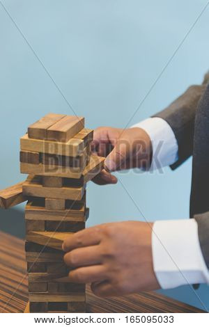 planning risk and strategy in business businessman gambling placing wooden block on a tower - blur for background