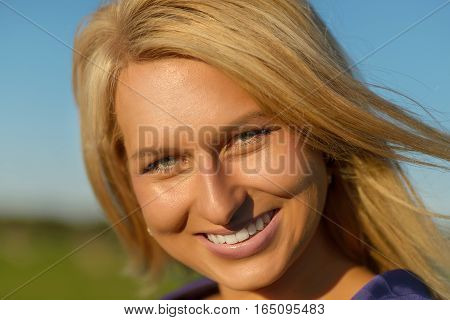 Sexy woman on hay stack on sunset. Beauty romantic girl outdoors against hay stack. Photo of sexy blond in a field with haystacks.