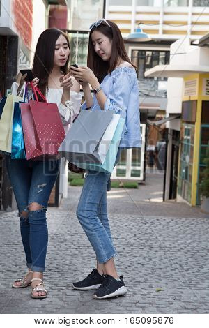 Two Beautiful Asian Shopaholic Women With Smartphone And Colorful Shopping Bags At Department Store