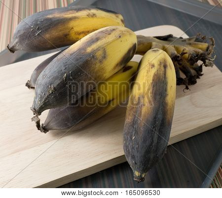 Fruits Bunch of Black Ripen Wild Banana Asian Banana or Cultivated Banana on A Wooden Cutting Board.