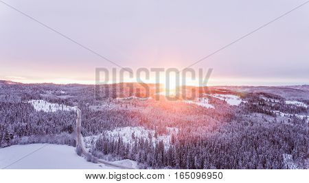 Idyllic winter sunrise. Aerial view over snowy, beautiful winter landscape in the heart of Norway.