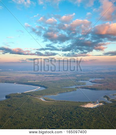 Aerial view over forest river in flood period. Oil rig is on the coast river.