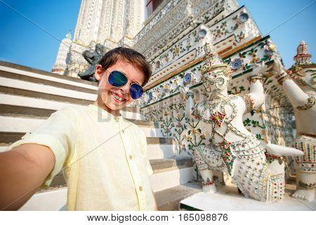 Cute little boy taking a selfie at temple Wat Arun, Thailand, Asia