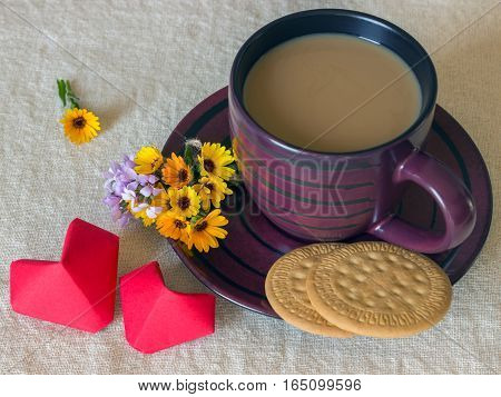 A small cup of coffee and two cookies. Bouquet of fresh wild flowers and a heart made of red paper. Valentine's Day. Concept - love.