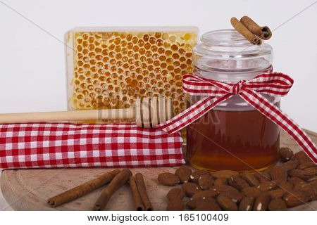 Honey in jar with honey dipper on a wooden background