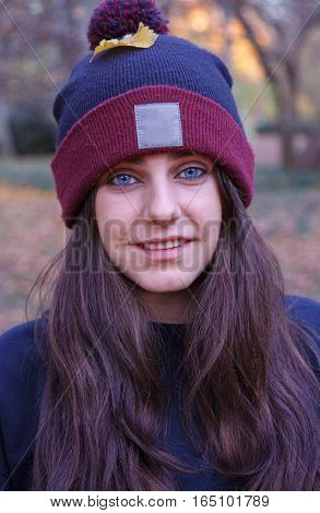 Portrait of a young Caucasian woman with blue eyes dressed in a wool cap with a white space where you can add information. She is in the field on an autumn day.