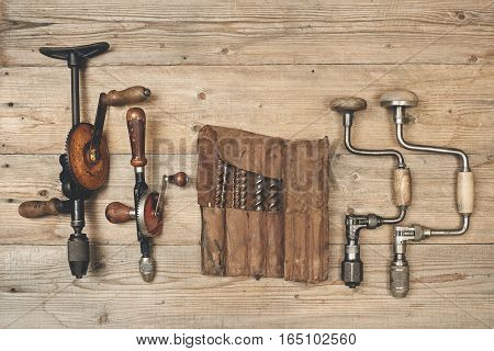 Drill braces with bits in leather tool roll on wooden workbench