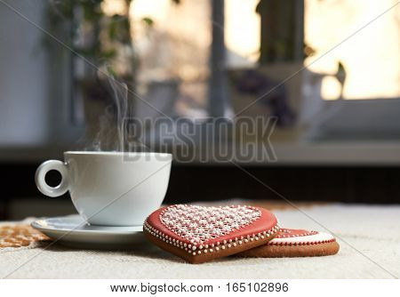 Steaming love. Cup of coffee steaming on the table heart shaped glazed cookies lying near