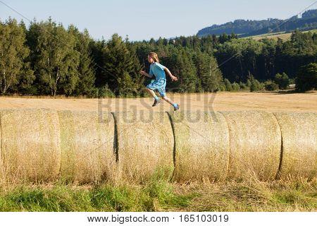 Boy Running on Bales of Hay in Summer