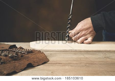 Carpenter's hand is ready to drill wood with auger bit