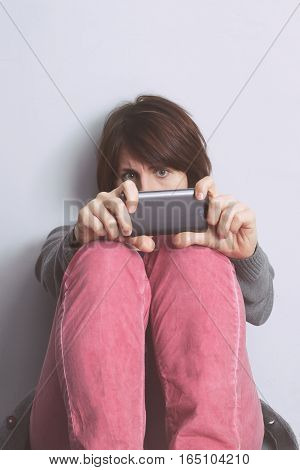 Girl Sitting Against A Wall And Holding A Smart Phone, Covering Her Face. Feeling Of Loneliness And