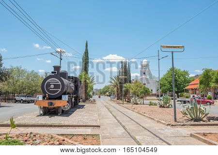 FAURESMITH SOUTH AFRICA - DECEMBER 31 2016: A steam locomotive and the town hall in Fauresmith one of only three towns on earth where the railway line runs down the centre of the main road