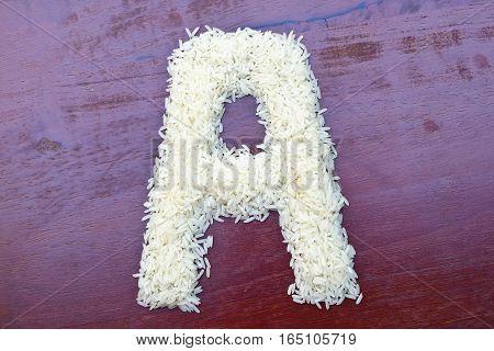 White rice grain alphabet letter isolated on wooden desks