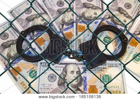 grid on the blurred background of money with handcuffs