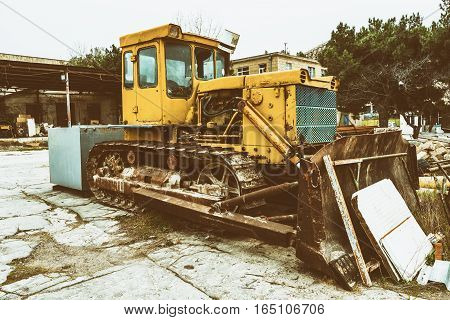 Old abandoned tractor bulldozer in plant yard