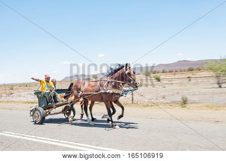 FAURESMITH SOUTH AFRICA - DECEMBER 31 2016: A friendly driver and companion on a horse drawn carriage in Fauresmith a small town in the Free State Province