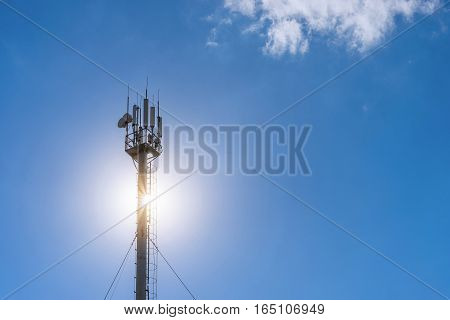 The antenna on the pole satellite communications cellular tower blue sky and sun. Concept communication
