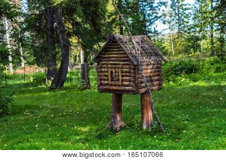 The wooden hut on legs. Fabulous a little house in the woods. Wooden decorative house lawn ornament