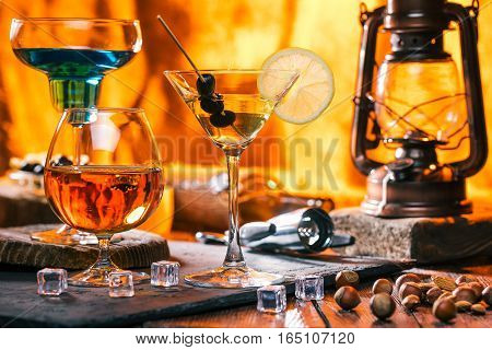 Cocktails in various shape glasses and nuts. Lamp and wine bottle behind them on bar counter