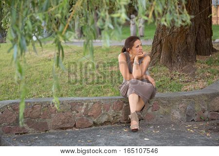 Girl Sitting On The Parapet Of The Summer In The Park