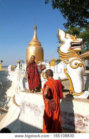 Bagan Myanmar 23 January 2010: Monks walking in front of Bu Paya pagoda at the archaeological site of Bagan on Myanmar