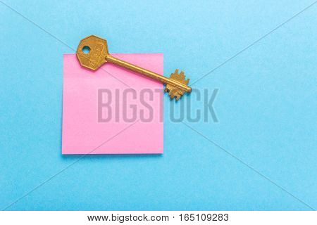 Adhesive note post and key on a blue background