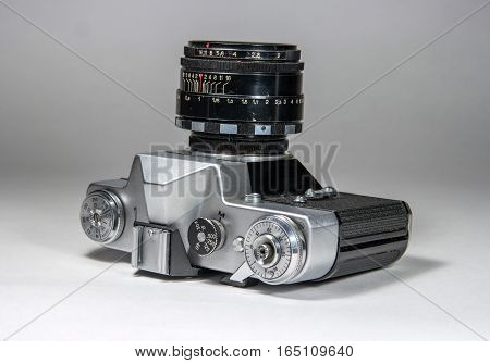 Old film camera photographed on a light background. The camera lens is up.